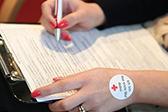 Foto: Frau füllt den Anamnesebogen des Blutspendedienstes aus - Ausschnitt der Hände und des Bogens.